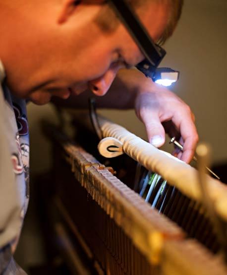 man repairing a classic upright piano